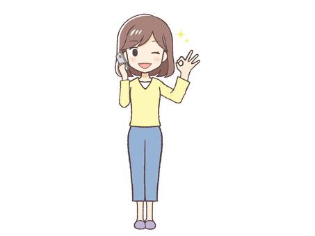 一個穿著便衣的女人在打電話時打著 OK 的手勢