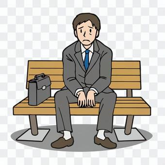 Depressed, tired man sitting on a park bench