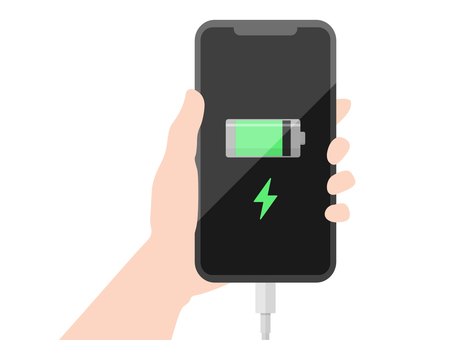 Hand holding a smartphone while charging