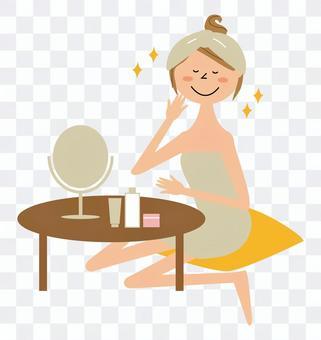 一個女人坐在鏡子前照顧她的皮膚