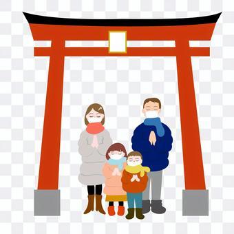 マスクをして初詣する家族と鳥居