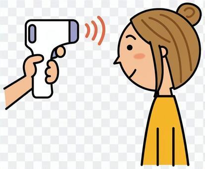 非接触体温計で熱を測る女性