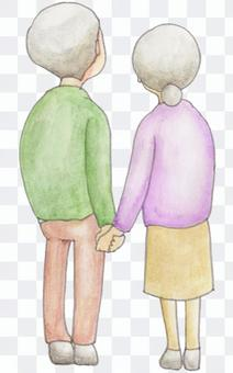 The back of the old couple holding hands