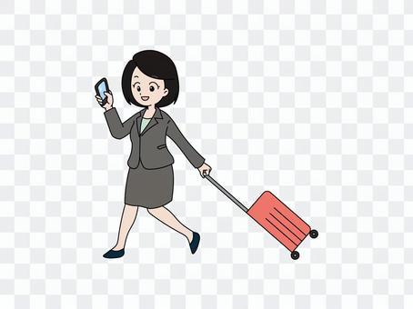 一個女人拿著智能手機,拉一個手提箱