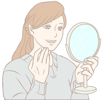一個微笑的女人看著手鏡(柔和的顏色)