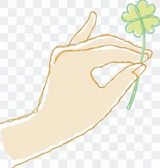 拿着四片叶子三叶草的手