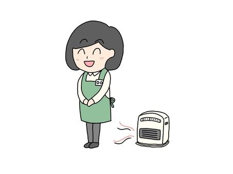 工作時用暖風機取暖的女人