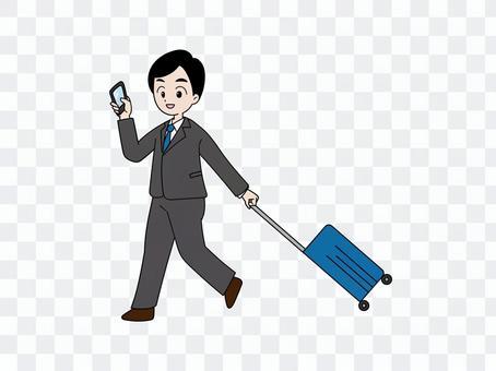一個男人拿著智能手機,拉著手提箱