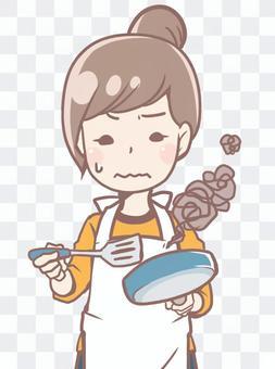 料理を失敗するお団子ヘア女性、主婦