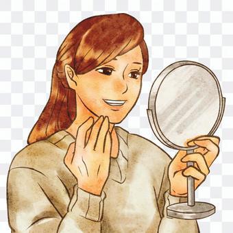 看在手鏡的一名微笑的婦女