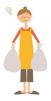 一個女人拿著垃圾袋心情不好