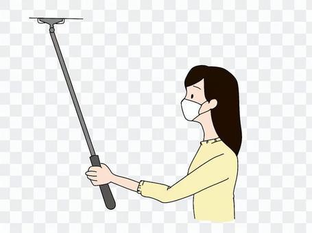 一個女人用地板刮水器清潔天花板