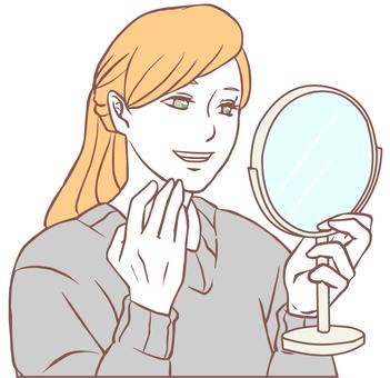 一個微笑的女人看著手鏡(簡單的顏色)