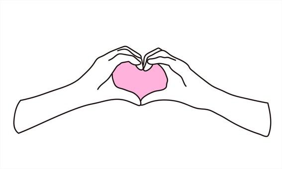 一個女人的手用她的手指做一個心形標記