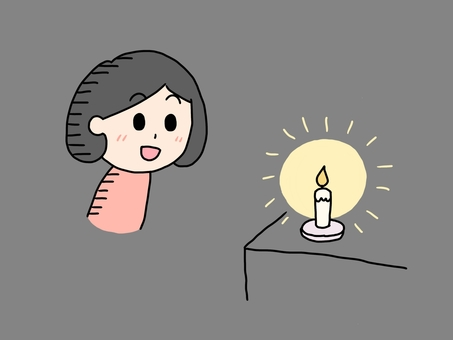 A woman watching a candle in the dark